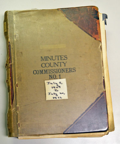 The Board of County Commissioners meeting minutes from July 5, 1909 to July 10, 1912 are archived in a book with a canvas cover and leather corners.