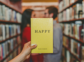 "Couple in the library and a hand holding the book ""Happy"""