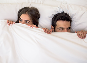 A man and woman in bed with white bed sheet up to their nose.