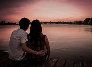A couple with their arms around each other looking at sunset.