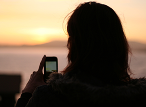 A woman on her cell phone with her back towards us  at sunset.