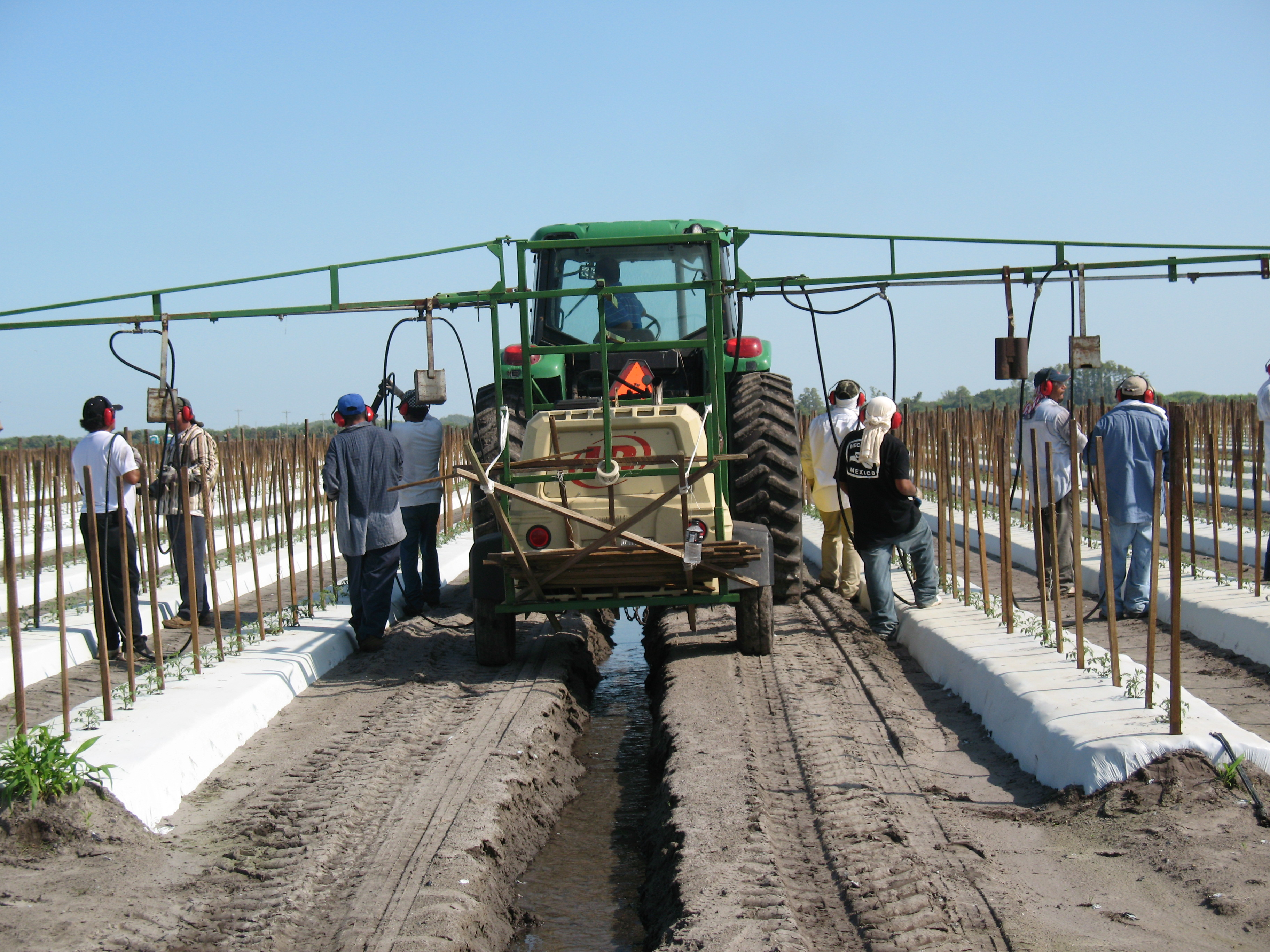Several workers surrounding tractor