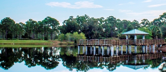 Picture of a covered fishing pier in the foreground and North Jupiter Flatwoods Natural Area in the background