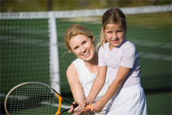 child with tennis instructor