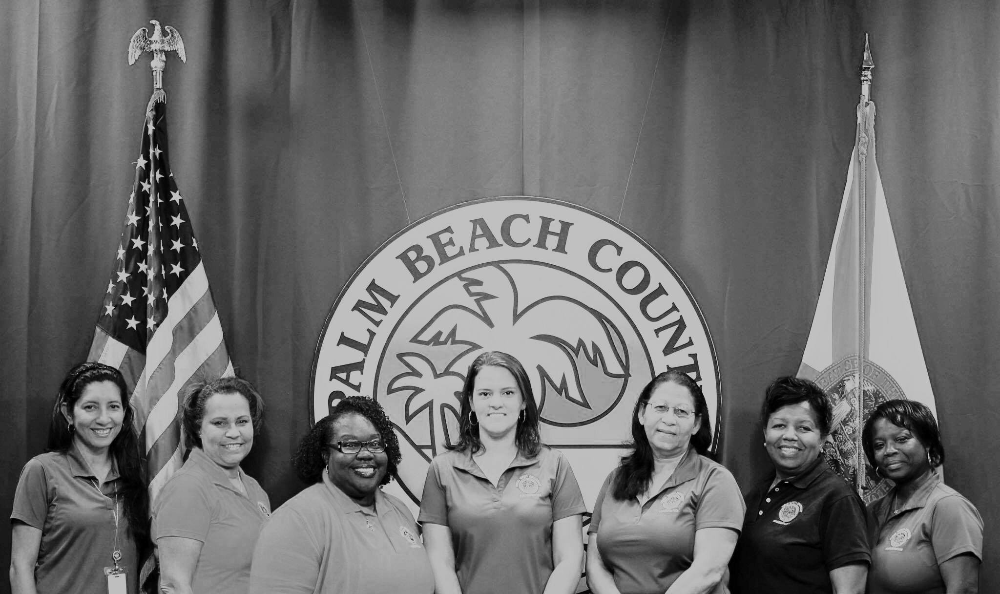 7 Female Admin Staff in front of County Logo