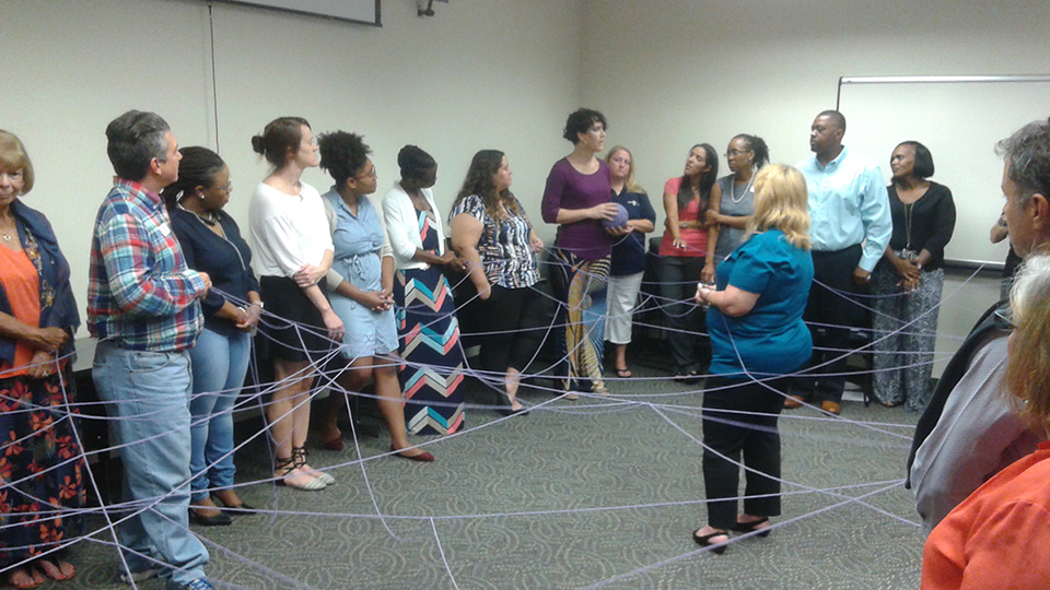 Participants holding string showing the connections between everyone